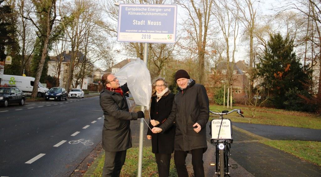 Bürgermeister Reiner Breuer (links), Umweltdezernent Dr. Matthias Welpmann und Henrike Mölleken, Leiterin des Amtes für Stadtgrün, Umwelt und Klima, enthüllen das Schild der EEA-Auszeichnung 2018 auf der Deutschen Straße.