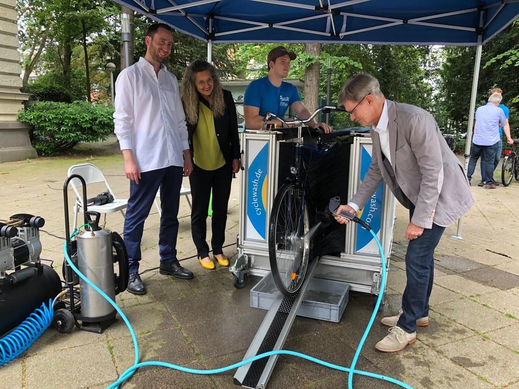 Dennis Fels (Klima-Team der Stadt) und Henrike Mölleken (Leitung Amt für Stadtgrün, Umwelt und Klima) schauen Stadtradel-Botschafter Mario Meyen beim Waschgang zu.