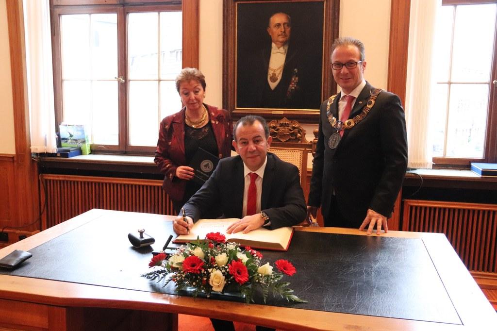 Tanju Özcan, Bürgermeister der befreundeten türkischen Stadt Bolu, trägt sich im Beisein von Bürgermeister Reiner Breuer und Angelika Quiring-Perl, Vorsitzende des Partnerschaftskomitees, in das Goldene Buch ein.