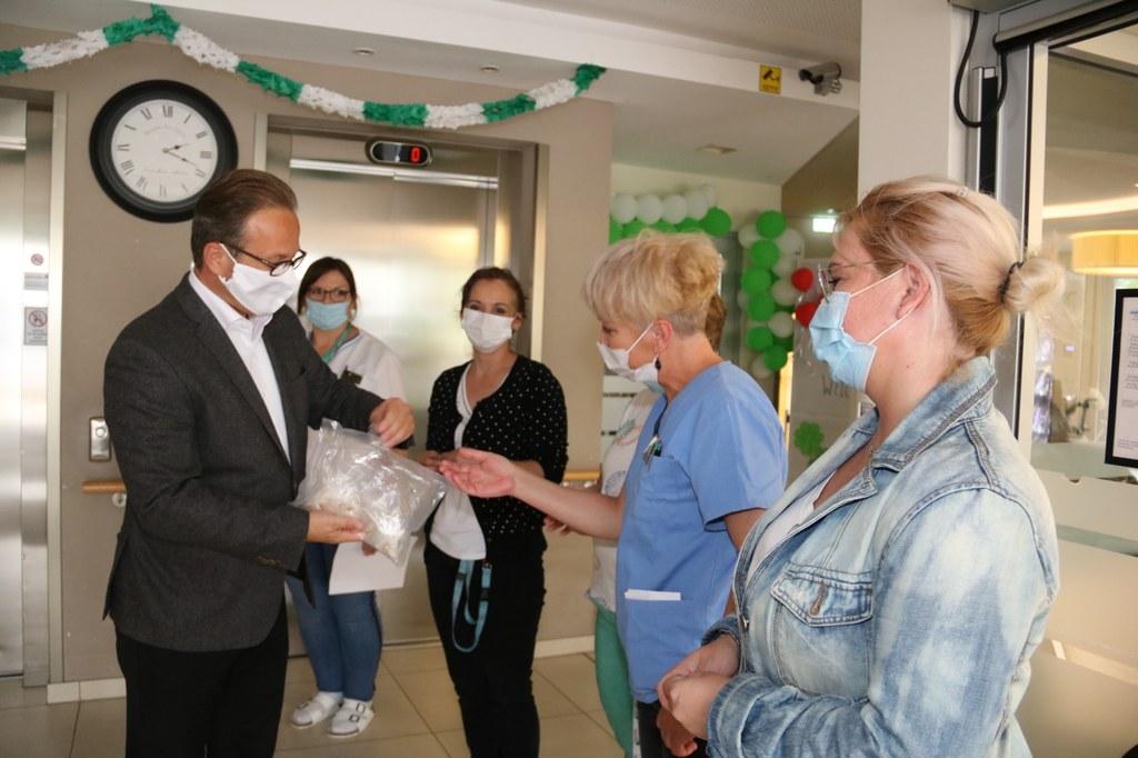 Bürgermeister Reiner Breuer verteilt Anstecknadeln mit dem Neusser Wappen an die Pflegekräfte.
