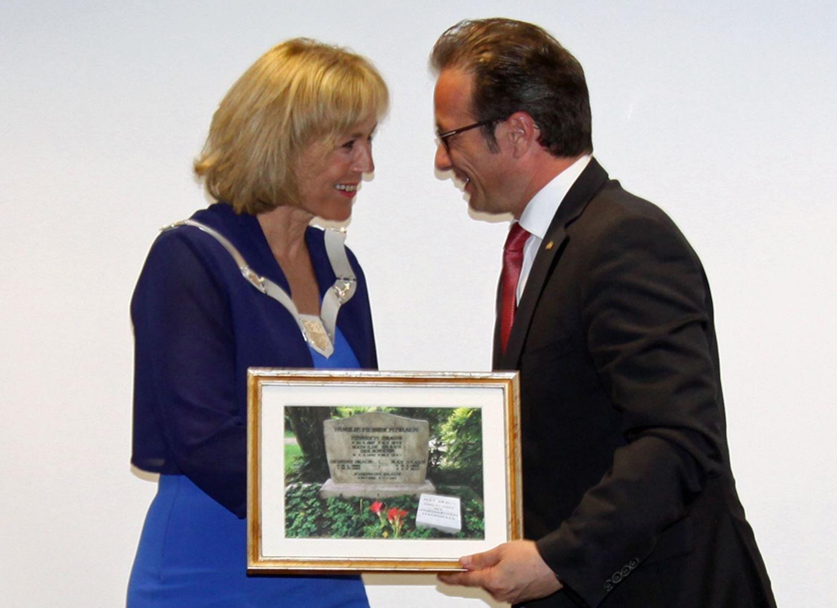 Bürgermeister Reiner Breuer überreichte seiner Kollegin Charlotte Britz, Oberbürgermeisterin von Saarbrücken, als Geschenk ein gerahmtes Bild von Max Brauns Grab, Foto: Landeshauptstadt Saarbrücken.