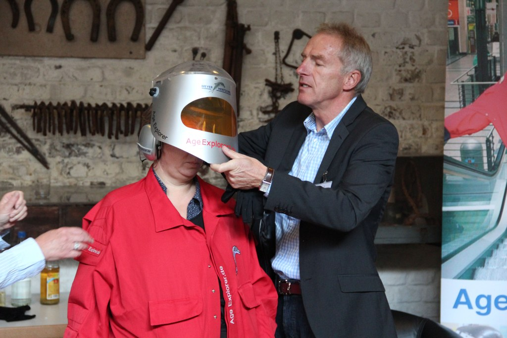 Lektorin Beate Kemper testet den Age Explorer. Heinz Einhaus, Mitarbeiter des Meyer-Hentschel Institut aus Saarbrücken, hilft ihr beim Anziehen.
