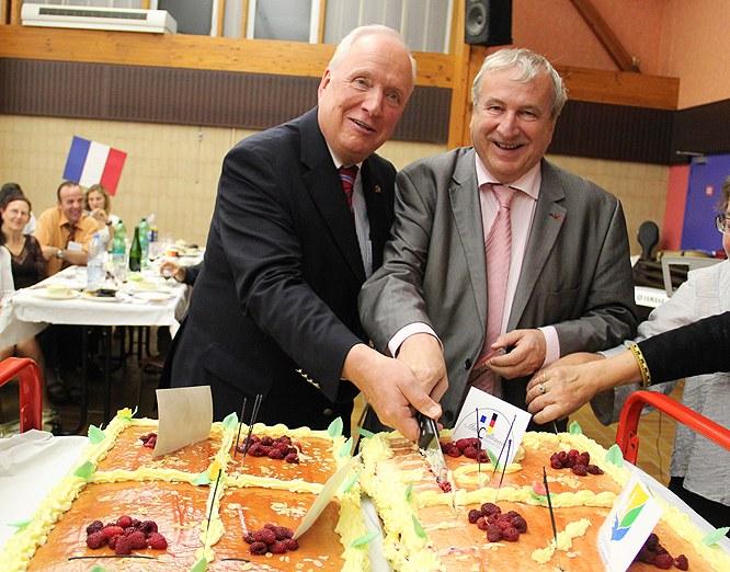 Bürgermeister Bruno Bourg-Broc und Erster Stellvertretender Neusser Bürgermeister Thomas Nickel schneiden gemeinsam die Geburtstagstorte an.